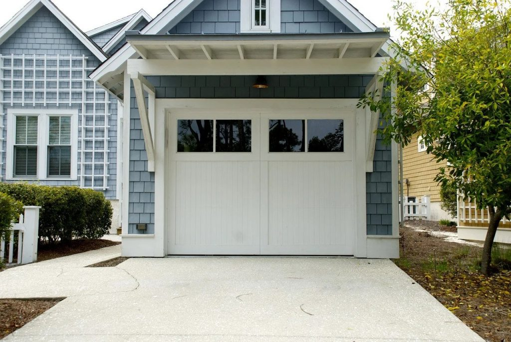 Light blue house with a new single car garage, garage door.